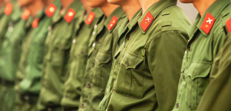 Jeune soldat vietnamien masculin dans l'uniforme vert dans une rangée, une étoile rouge et une icône croisée d'épées dans les rub images libres de droits