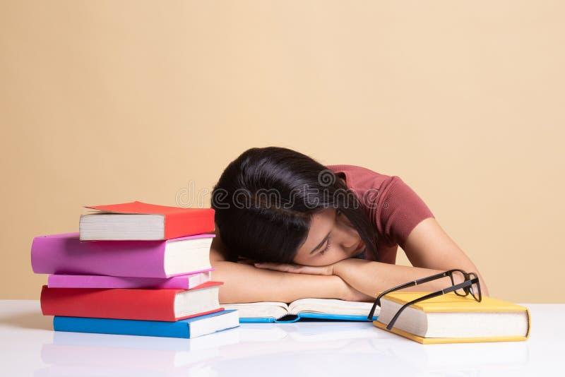 Jeune sommeil asiatique ?puis? de femme avec des livres sur la table images libres de droits