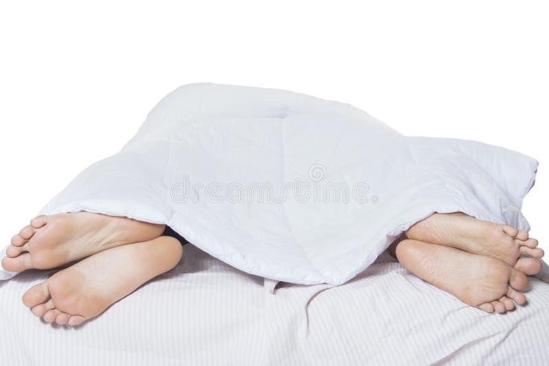 Jeune sommeil de couples distinct sur le lit photographie stock
