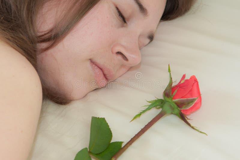 Jeune sommeil de femme et une rose photographie stock