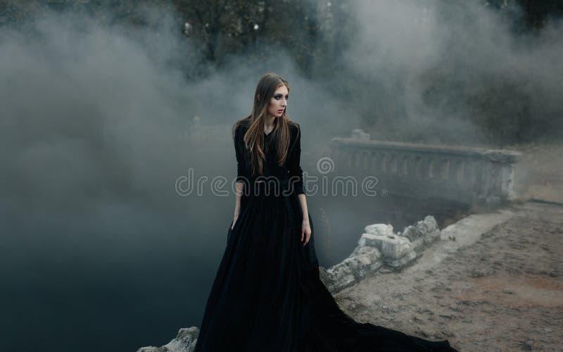 Jeune sorcière attirante marchant sur le pont dans la fumée noire lourde photographie stock libre de droits