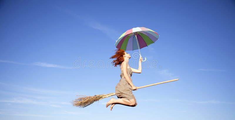 Jeune sorcière red-haired sur le vol de balai dans le ciel images libres de droits