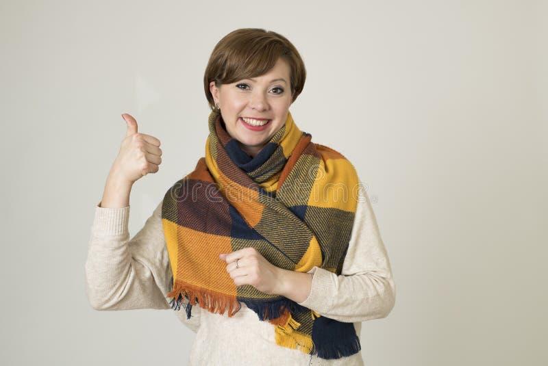Jeune sourire coloré de beaux et élégants chandail de femme des cheveux 30s et écharpe rouges d'automne heureux photo stock