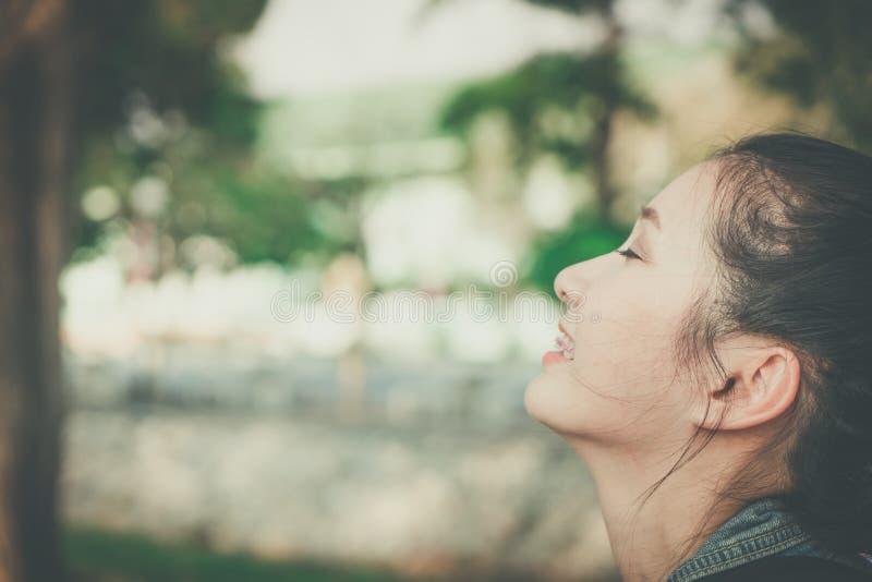 Jeune sourire heureux de visage de femme avec la gomme en nature prendre un sentiment de respiration profonde frais o photo stock