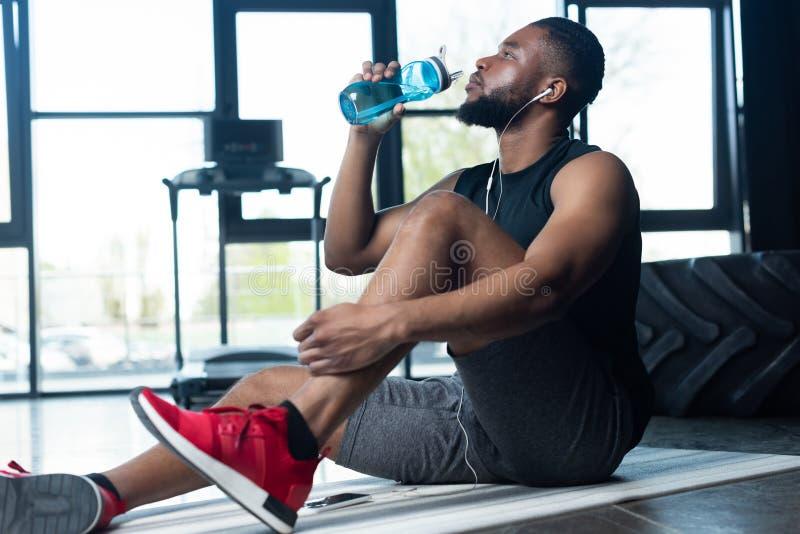 jeune sportif d'afro-américain dans des écouteurs se reposant sur le tapis de yoga et l'eau potable  photographie stock libre de droits
