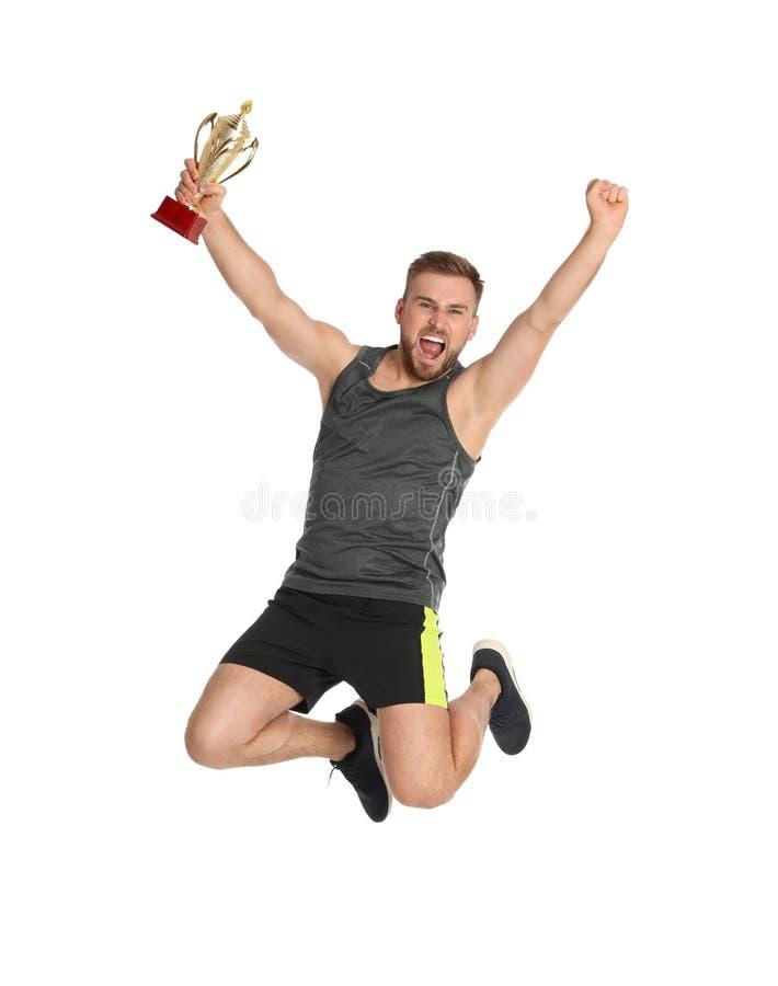 Jeune sportif enthousiaste avec la tasse de trophée d'or sautant sur le blanc photos stock