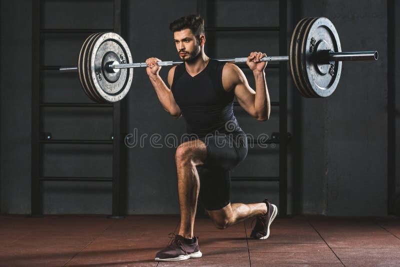 Jeune sportif faisant l'exercice avec le barbell sur des épaules photographie stock