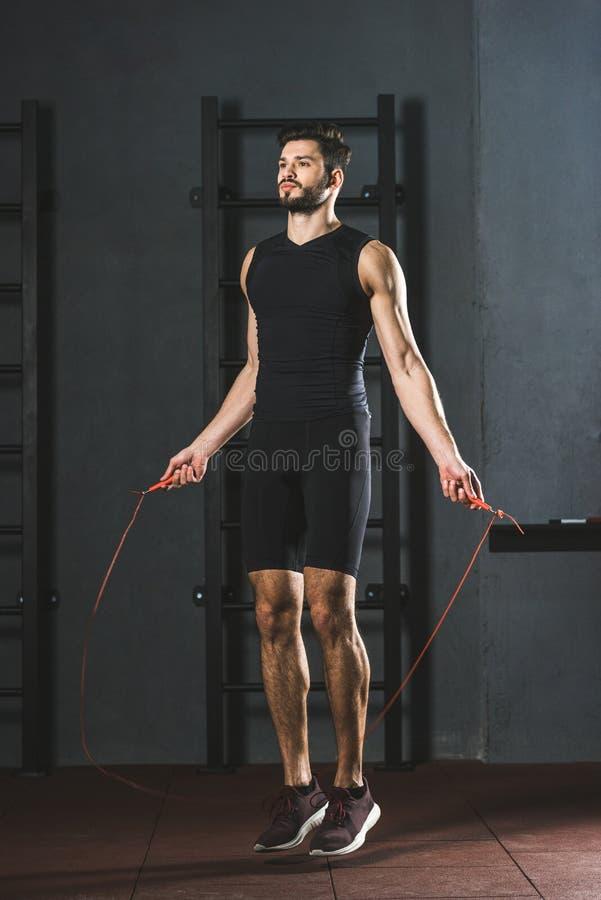 Jeune sportif faisant la séance d'entraînement de corde de saut images stock