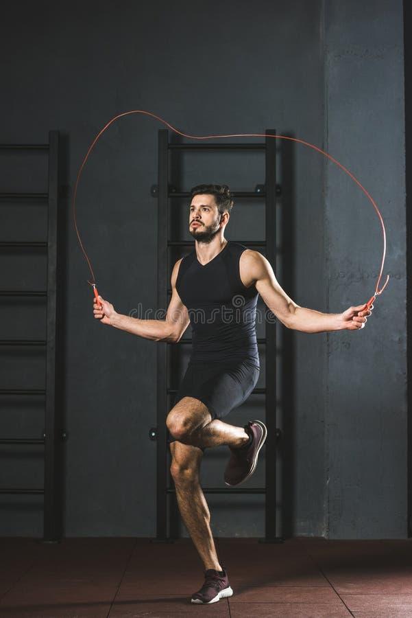 Jeune sportif faisant la séance d'entraînement de corde de saut image stock