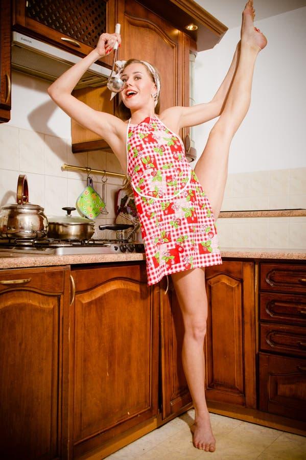 Jeune sportif, flexible, fille blonde de femme de goupille- au fourneau goûte la soupe avec le scoop ou la poche images libres de droits