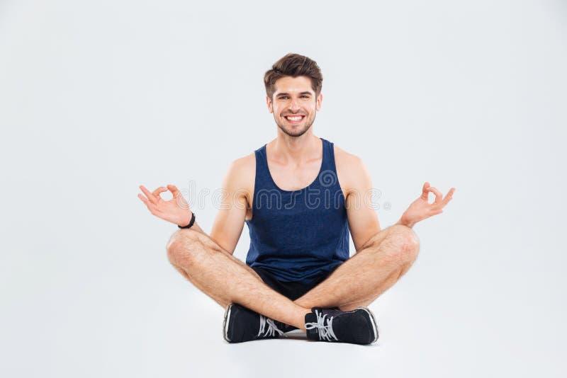 Jeune sportif heureux s'asseyant dans la pose et le sourire de lotus photographie stock libre de droits