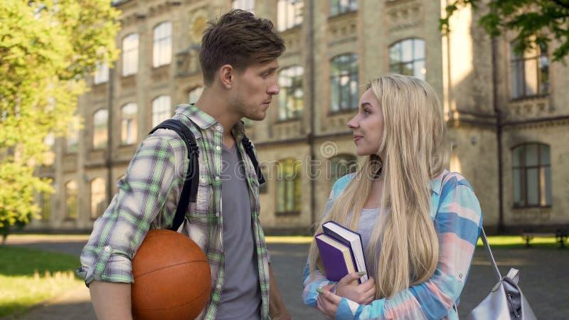 Jeune sportif parlant avec la belle université proche blonde, demandant la date photos stock
