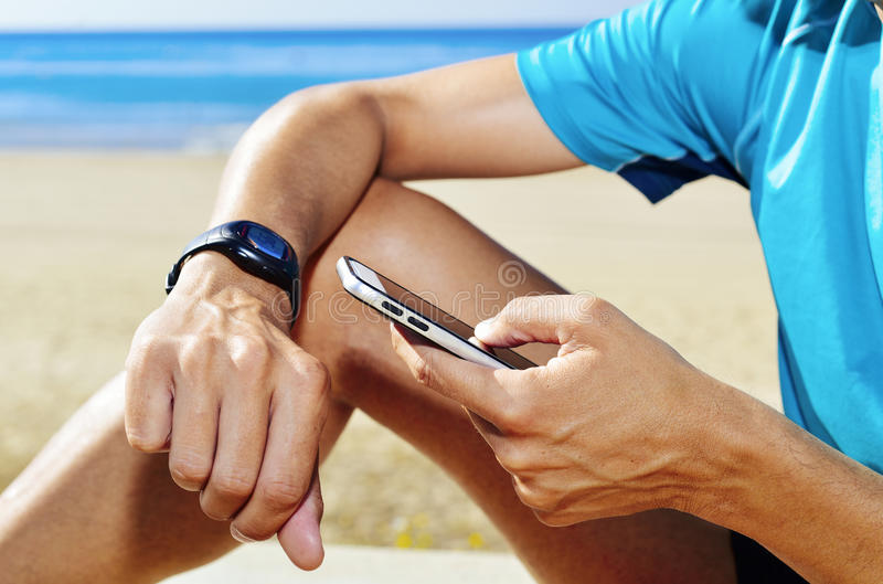 Jeune sportif syncing son smartwatch photographie stock