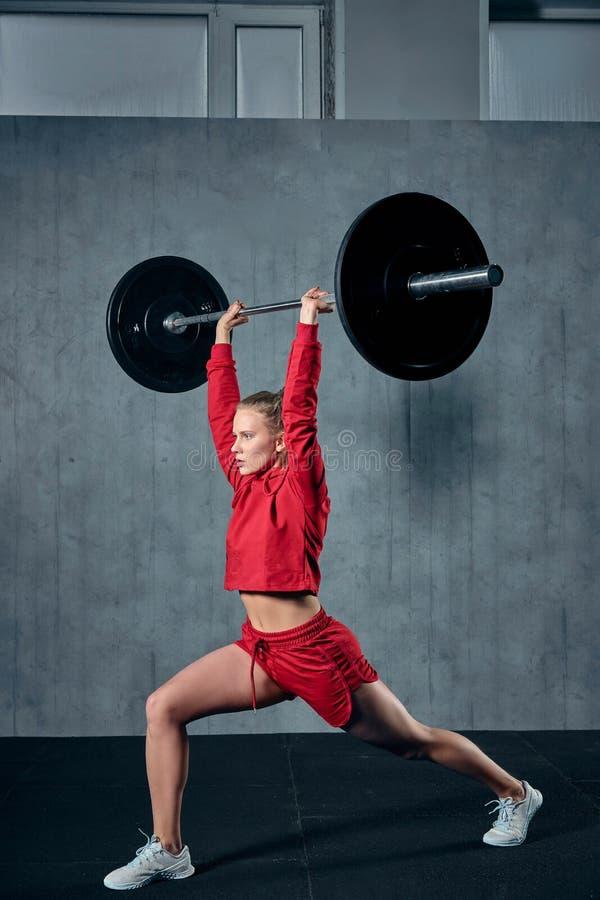 Jeune sportive tendue prête à exécuter l'exercice de presse d'épaule avec le barbell lourd images stock