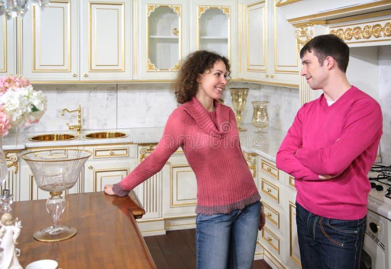 Jeune stand de couples sur la cuisine image stock