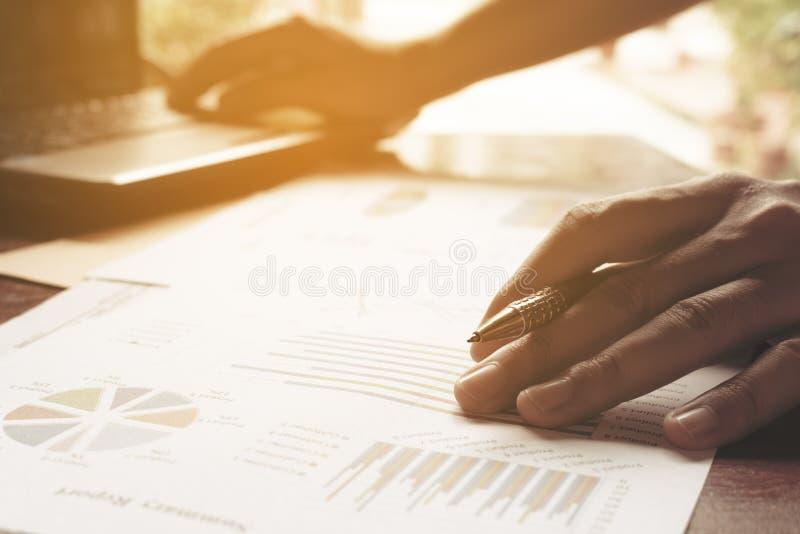 Jeune stylo de participation d'homme d'affaires sur les diagrammes et le graphique pour découvrir le Th photo stock