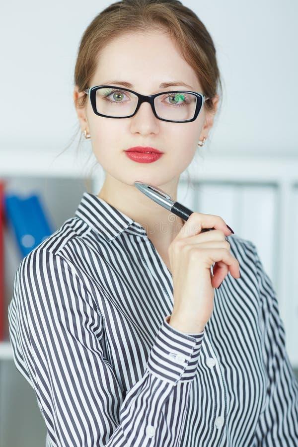 Jeune stylo de participation de femme d'affaires près du visage regardant in camera le portrait photographie stock libre de droits