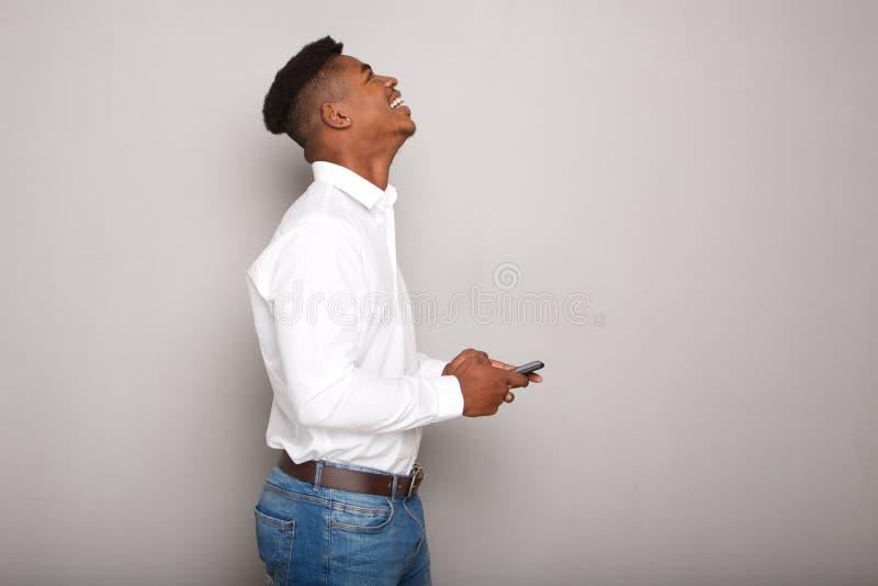 Jeune téléphone portable heureux de participation d'homme de couleur par le mur gris photo stock