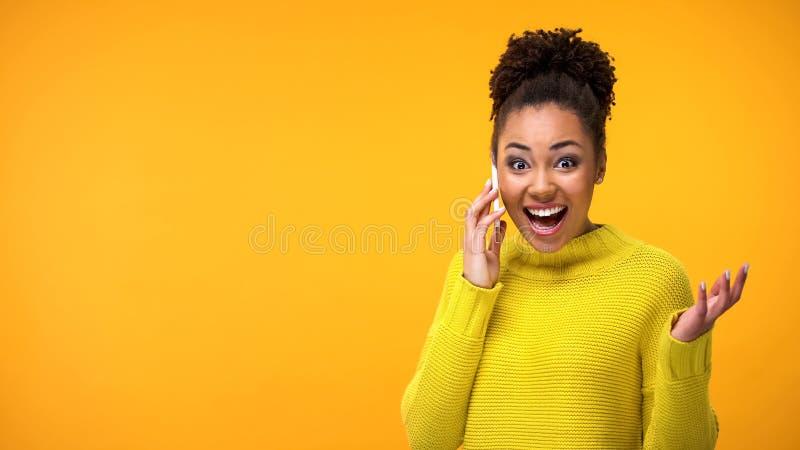 Jeune t?l?phone parlant femelle heureux semblant nouvelles excit?es et bonnes, approbation de succ?s photo stock