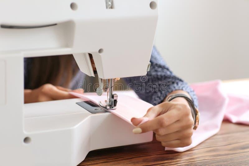 Jeune tailleur féminin utilisant la machine à coudre, plan rapproché photo libre de droits