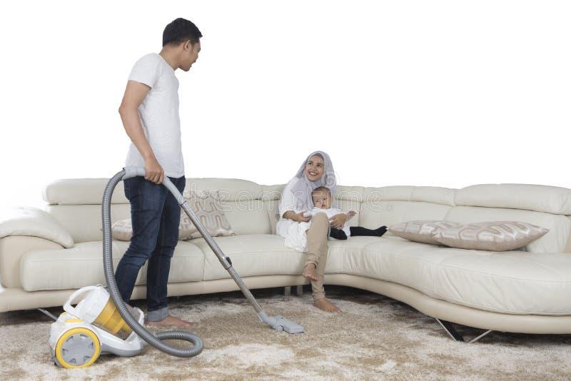 Jeune tapis de nettoyage de mari avec l'aspirateur image stock