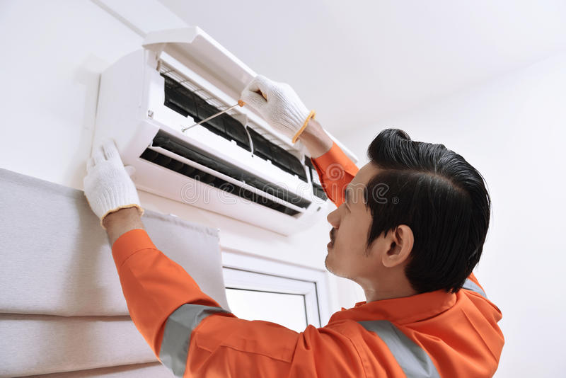 Jeune technicien masculin asiatique réparant le climatiseur avec la vis photos libres de droits