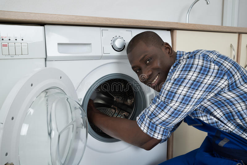 Jeune technicien masculin Fixing Washing Machine images libres de droits