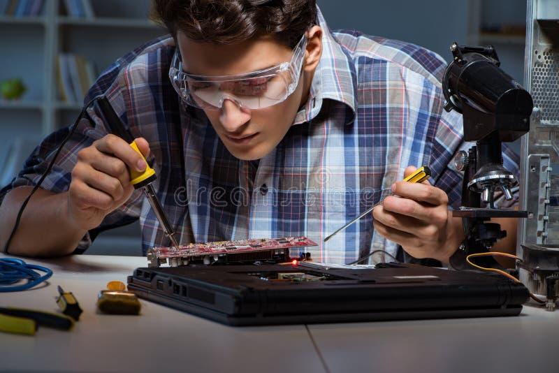 Jeune technicien-réparateur PL in FR has S on both words soudant les parties électriques sur motherboar images stock