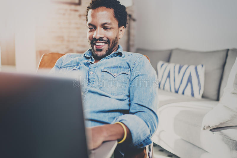Jeune temps de repos africain barbu heureux de dépense d'homme à la maison et à l'aide de l'ordinateur portable Concept des perso image stock
