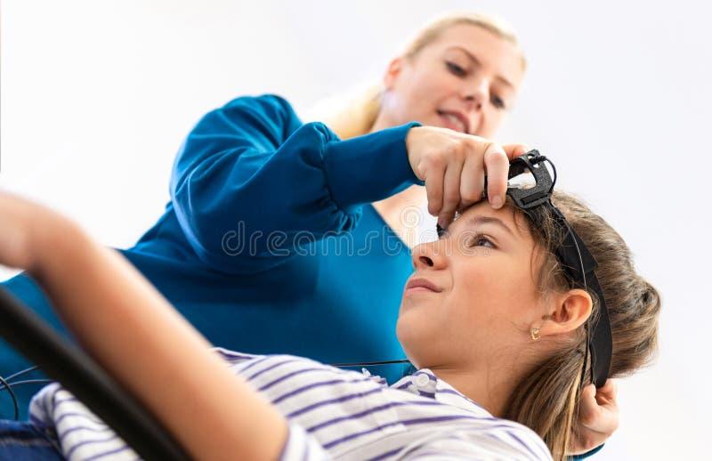 Jeune thérapeute d'adolescente et d'enfant pendant la session de neurofeedback d'EEG Concept d'électroencéphalographie photographie stock