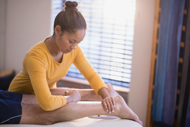 Jeune thérapeute féminin massant le veau du patient masculin photo libre de droits