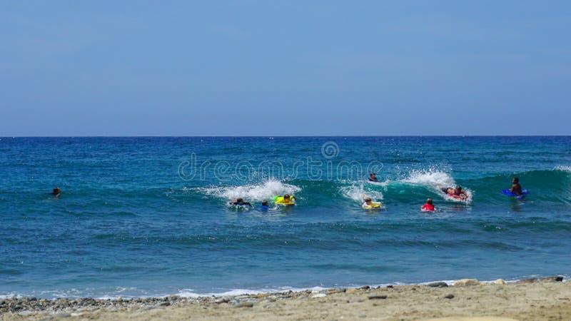 Jeune tombola de surfers les vagues d'une plage des Caraïbes un beau jour ensoleillé images libres de droits