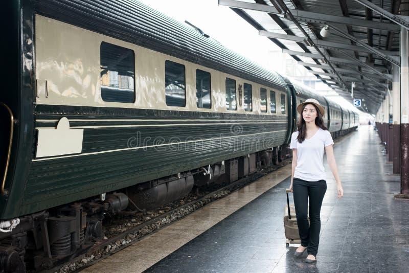 Jeune touriste asiatique avec le train de attente de bagage dans la station image stock