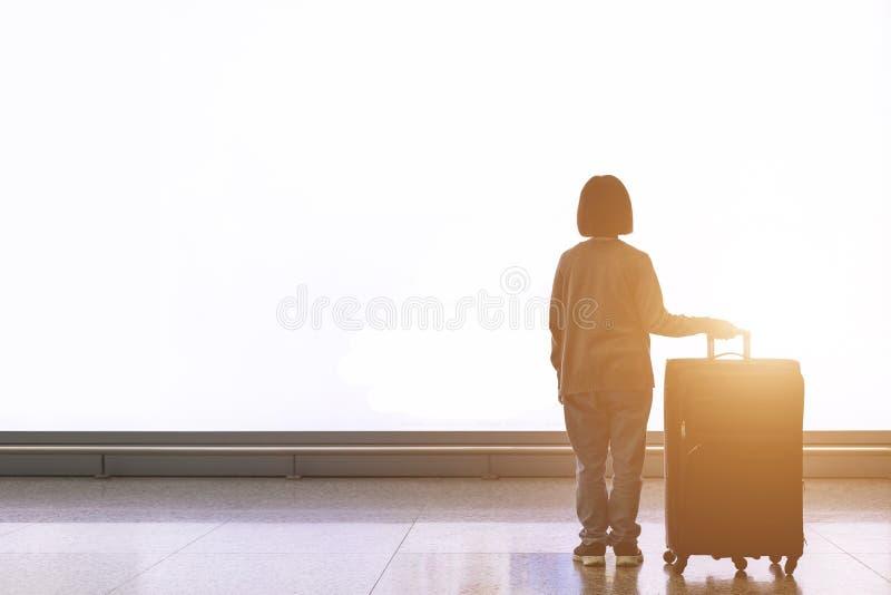 Jeune touriste avec le bagage se tenant devant le grand panneau d'affichage léger blanc à l'aéroport image libre de droits