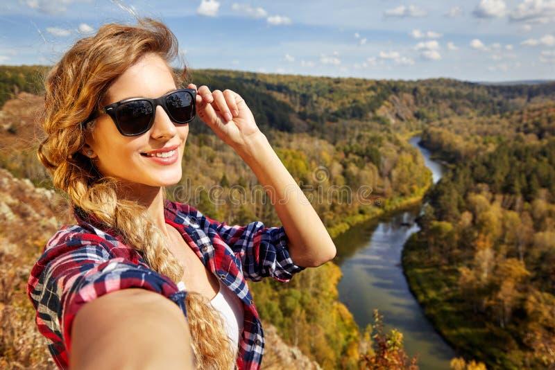 Jeune touriste blonde de femme sur une falaise prenant la photo de selfie dessus photographie stock libre de droits