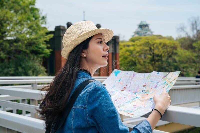 Jeune touriste de femme élégante tenant une carte de papier et recherchant la bonne manière voyageur féminin environnant d'arbres image libre de droits