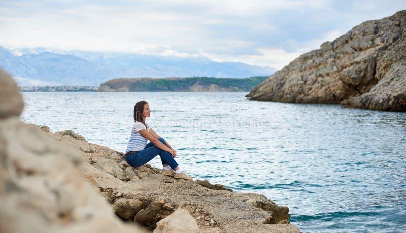 Jeune touriste féminin attirant dans les jeans et le T-shirt seul se reposant sur le rivage pierreux de la mer image stock