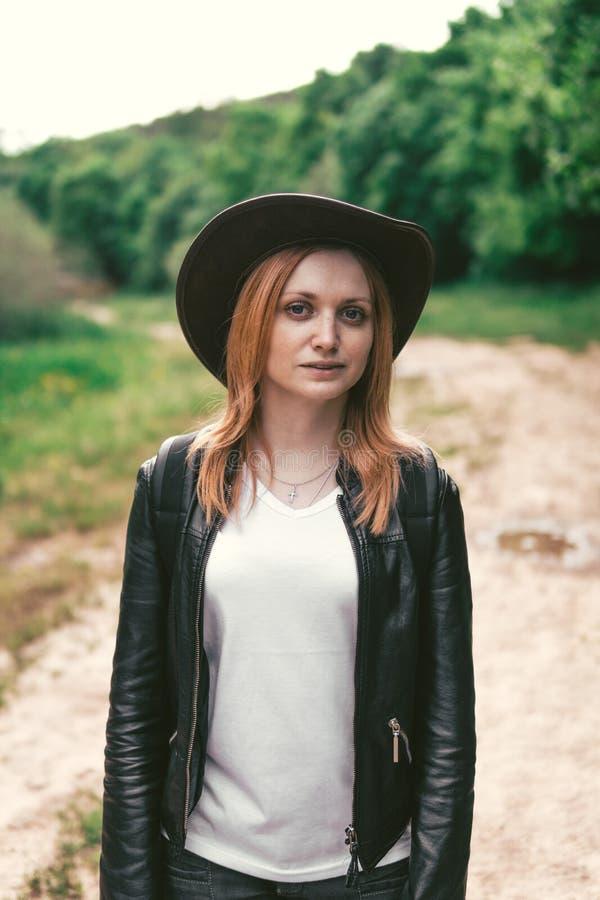 Jeune touriste féminin avec un sac à dos rose et un chapeau en cuir de style de cowboy regardant la distance Portrait concept d'a photographie stock libre de droits