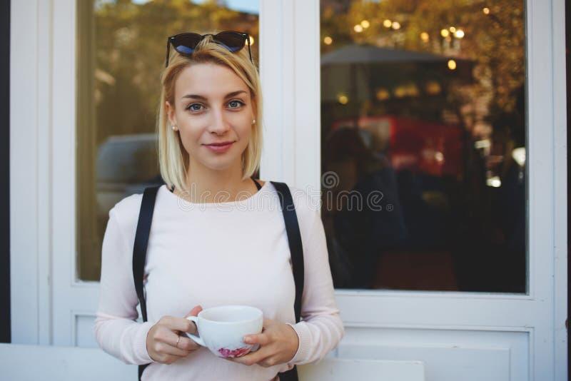 Jeune touriste féminin magnifique avec la tasse de thé vert dans des mains se reposant dans le restaurant confortable après excur image stock