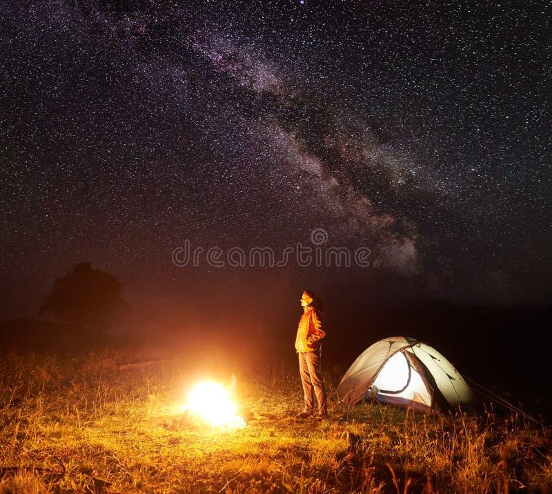 Jeune touriste féminin se tenant près de la tente lumineuse, campant en montagnes la nuit sous le ciel étoilé photo libre de droits