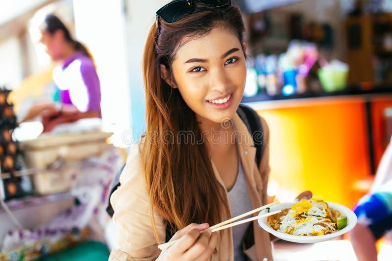 Jeune touriste f?minin mangeant la nouille tha?landaise de protection au magasin photos libres de droits