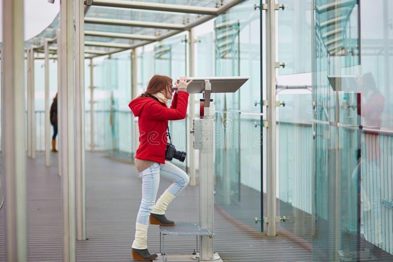 Jeune touriste gai à l'aide du télescope photographie stock