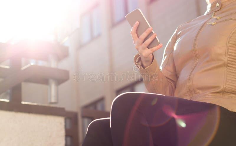 Jeune transmission de messages urbaine de femme avec le smartphone dans le coucher du soleil ou le lever de soleil Style de vie m photos stock