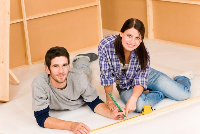 Jeune travail de couples d'amélioration de l'habitat sur des rénovations photos libres de droits