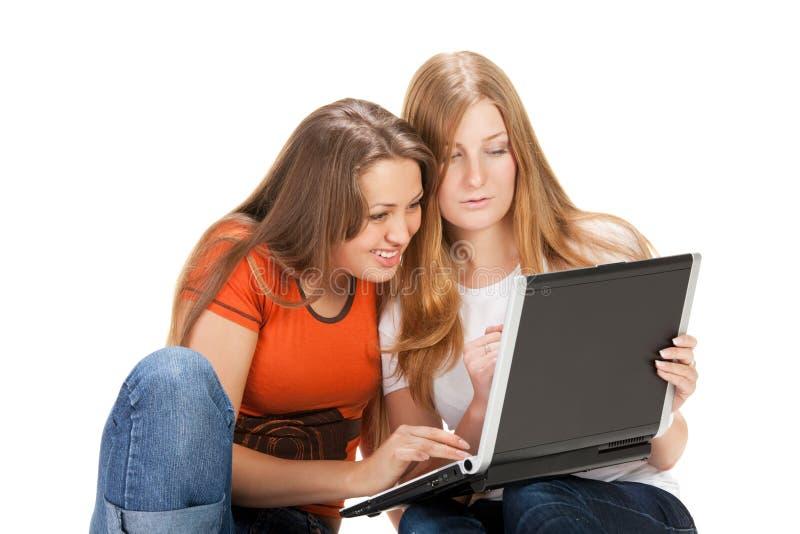 Jeune travail heureux de fille de l'étudiant deux sur l'ordinateur portatif images libres de droits