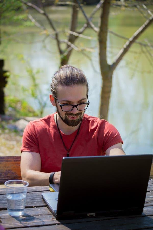 Jeune travailler de sourire de concepteur d'indépendant d'homme extérieur par le lac le jour ensoleillé d'été de ressort d'ordina photos stock