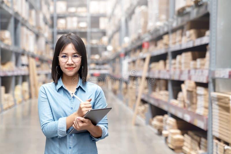 Jeune travailleur asiatique attirant, propriétaire, femme d'entrepreneur tenant le comprimé intelligent regardant la caméra avec  images stock