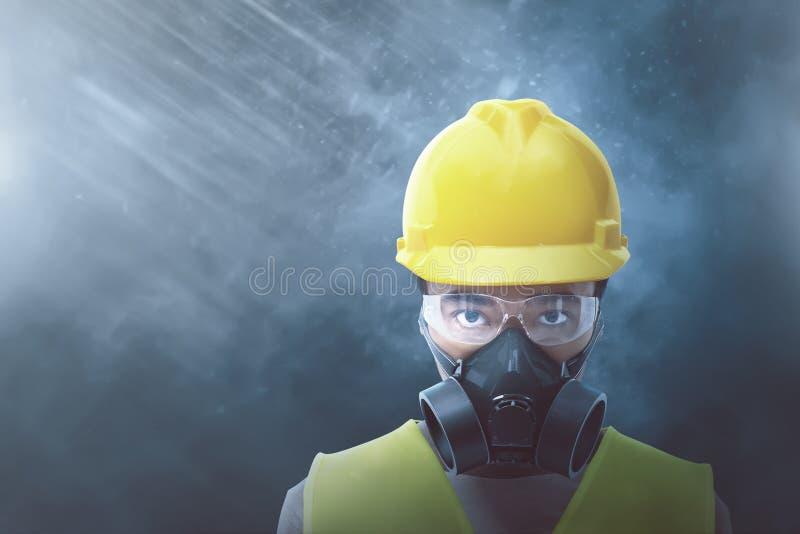 Jeune travailleur asiatique avec le casque jaune et le masque protecteur photo stock