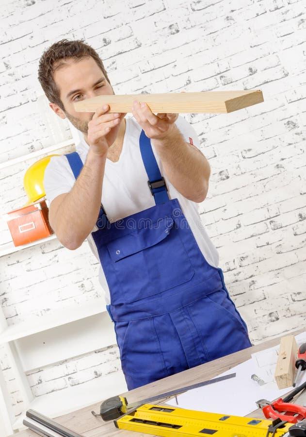 Jeune travailleur avec un conseil en bois image libre de droits