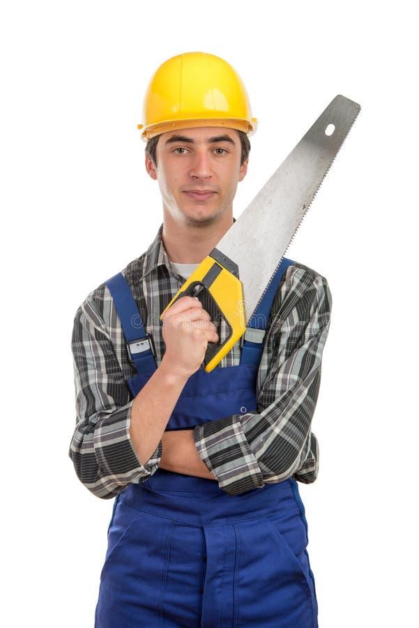Jeune travailleur avec une scie à main photos libres de droits